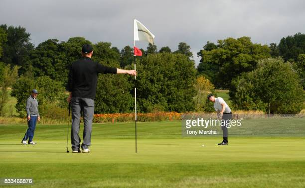 Alexander Shaw of Ingleby Barwick Golf Academy putts as James Harper of The Wynyard Club tends the flag during the Golfbreakscom PGA Fourball...