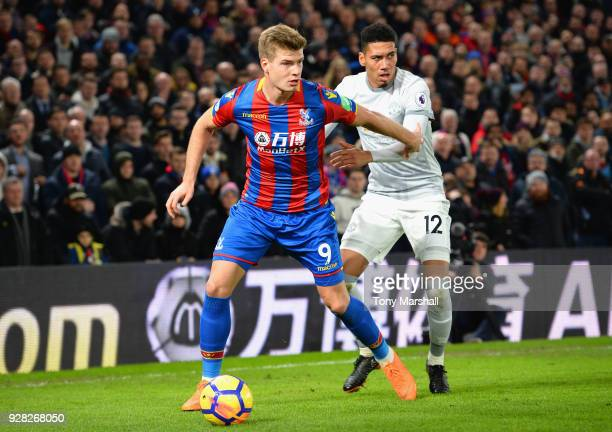 Alexander Sorloth of Crystal Palace holds off a challenge from Chris Smalling of Manchester United during the Premier League match between Crystal...