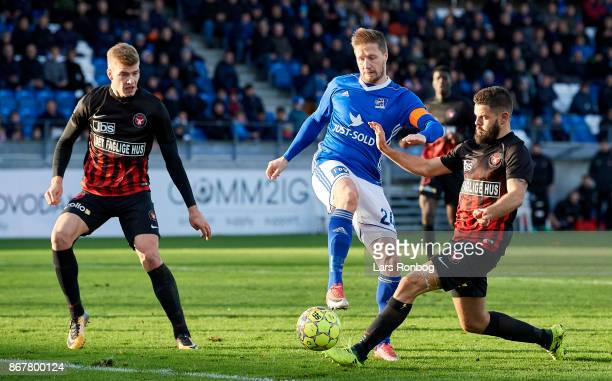 Alexander Sorloth of FC Midtjylland Thomas Sorensen of Lyngby BK and Marc Dal Hende of FC Midtjylland compete for the ball during the Danish Alka...