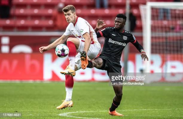 Alexander Sorloth of Leipzig is challenged by Edmond Tapsoba of Leverkusen during the Bundesliga match between Bayer 04 Leverkusen and RB Leipzig at...