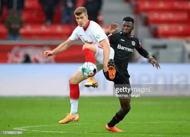 Alexander Sorloth of RB Leipzig is challenged by Edmond Tapsoba of Bayer 04 Leverkusen during the Bundesliga match between Bayer 04 Leverkusen and RB...
