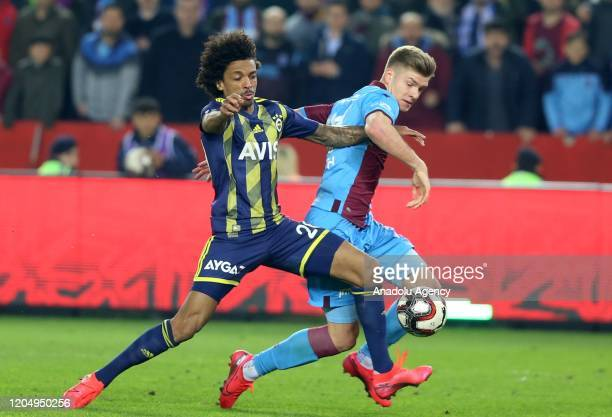 Alexander Sorloth of Trabzonspor is in action against Luiz Gustavo of Fenerbahce during the Ziraat Turkish Cup semifinal first leg match between...