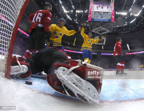 Alexander Steen and Patrik Berglund of Sweden celebrate a goal by Daniel Alfredsson in the third period against Reto Berra of Switzerland during the...
