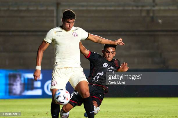 Alexander Succar of of Club Universitario de Deportes competes for the ball with Nicolás Romat pf Club Atlético Huracán during a friendly match...
