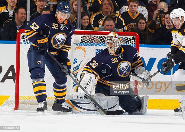 Alexander Sulzer and Ryan Miller of the Buffalo Sabres defend against the Boston Bruins on December 19 2013 at the First Niagara Center in Buffalo...