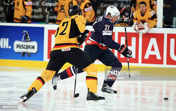 Alexander Sulzer of Germany and Kyle Okposo of USA compete for the puck during the IIHF World Championship group D match between USA and Germany at...