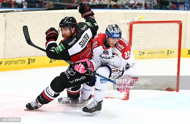 Alexander Sulzer of Koelner Haie skates against Barry Tallackson of Eisbaeren Berlin during the DEL Ice Hockey match between Koelner Haie and...