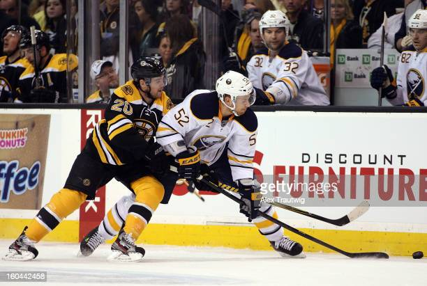 Alexander Sulzer of the Buffalo Sabres and Daniel Paille of the Boston Bruins battle for the puck during a game at the TD Garden on January 31 2013...