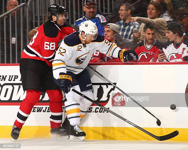 Alexander Sulzer of the Buffalo Sabres and Jaromir Jagr of the New Jersey Devils fight for the puck in the second period at Prudential Center on...