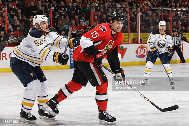 Alexander Sulzer of the Buffalo Sabres defends against Zack Smith of the Ottawa Senators during an NHL game at Canadian Tire Centre on February 6...