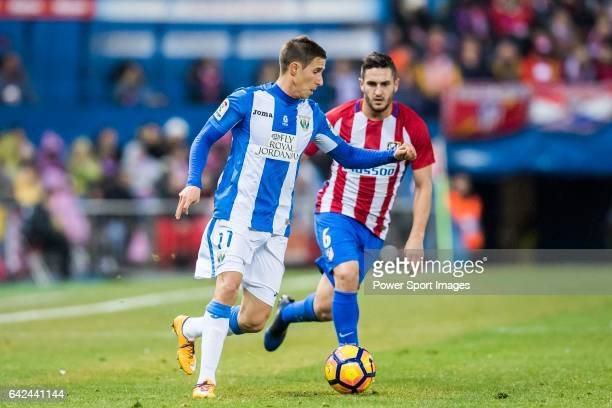 Alexander Szymanowski of Deportivo Leganes is chased by Jorge Resurreccion Merodio Koke of Atletico de Madrid during their La Liga match between...