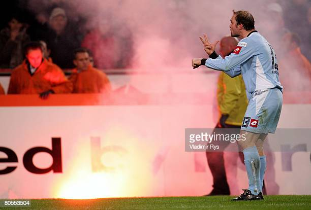 Alexander Voigt of Gladbach gestures towards Gladbach fans as a sign flare lays on the pitch shortly before the end of the Second Bundesliga match...