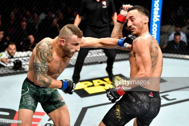 Alexander Volkanovski of Australia punches Max Holloway in their UFC featherweight championship bout during the UFC 245 event at TMobile Arena on...