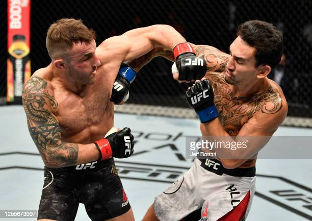 Alexander Volkanovski of Australia punches Max Holloway in their UFC featherweight championship fight during the UFC 251 event at Flash Forum on UFC...