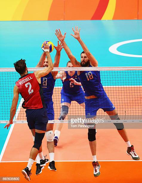 Alexander Volkov of Russia and Alexander Volkov of Russia try to block the spike of Aaron Russell of United States during the Men's Bronze Medal...
