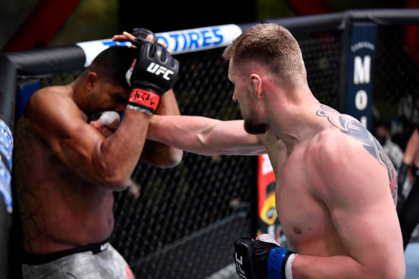 Alexander Volkov of Russia punches Alistair Overeem of the Netherlands in their heavyweight fight during the UFC Fight Night event at UFC APEX on...