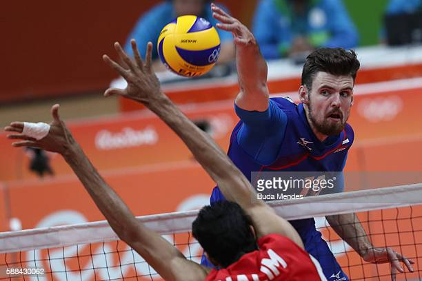 Alexander Volkov of Russia spikes the ball against Abd Halim of Egypt during the men's qualifying volleyball match between Russia and Egypt on Day 6...