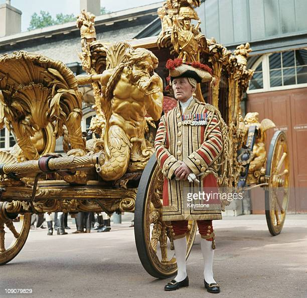 Alexander Weddle one of the State Coachmen stands beside the State Coach at the Royal Mews Buckingham Palace in his livery circa 1980