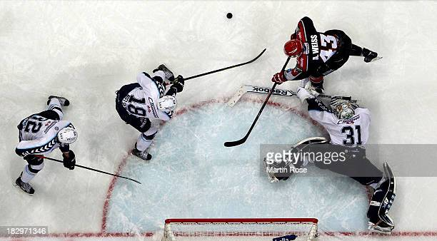 Alexander Weiss of Koeln fails to score over Niklas Treutle goaltender of Hamburg during the DEL match between Koelner Haie and Hamburg Freezers at...