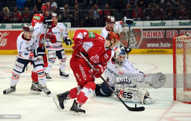 Alexander Weiss of Koeln is challenged by goalkeeper Robert Zepp of Berlin during the DEL match between Koelner Haie and Eisbaeren Berlin at Lanxess...