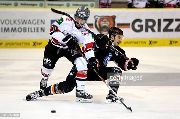 Alexander Weiss of Wolfsburg and Christian Ehrhoff of Koeln battle for the puck during the DEL match between Grizzly Wolfsburg and Koelner Haie at...