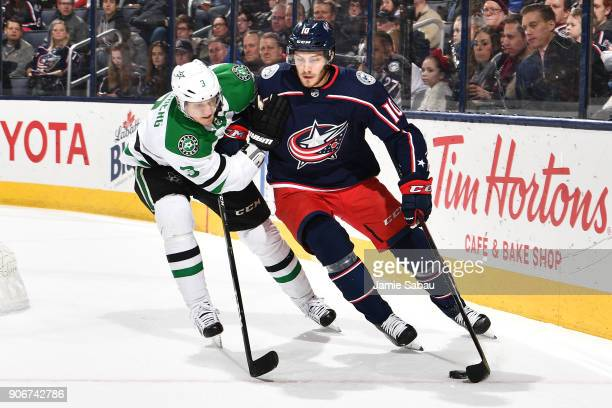 Alexander Wennberg of the Columbus Blue Jackets attempts to keep the puck from John Klingberg of the Dallas Stars during the first period of a game...