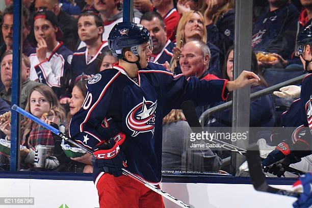 Alexander Wennberg of the Columbus Blue Jackets hands his front tooth to a trainer after losing it to a high stick in the second period of a game...