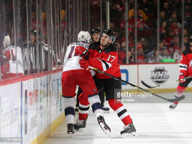 Alexander Wennberg of the Columbus Blue Jackets is checked by Kenny Agostino of the New Jersey Devils during the third period at the Prudential...
