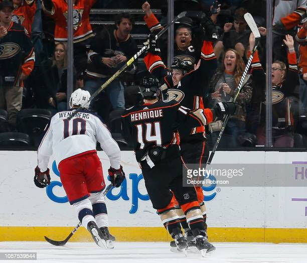 Alexander Wennberg of the Columbus Blue Jackets reacts as Adam Henrique and Cam Fowler of the Anaheim Ducks celebrate Fowler's hat trick gamewinning...