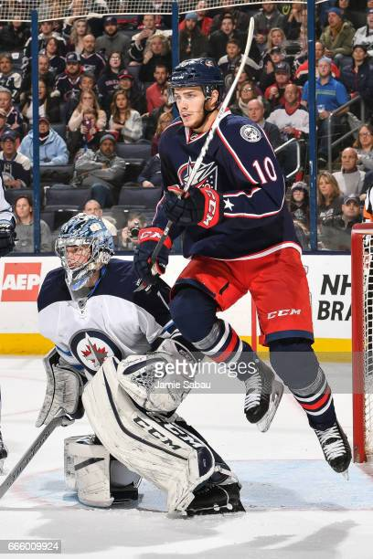 Alexander Wennberg of the Columbus Blue Jackets skates past goaltender Eric Comrie of the Winnipeg Jets on April 6 2017 at Nationwide Arena in...