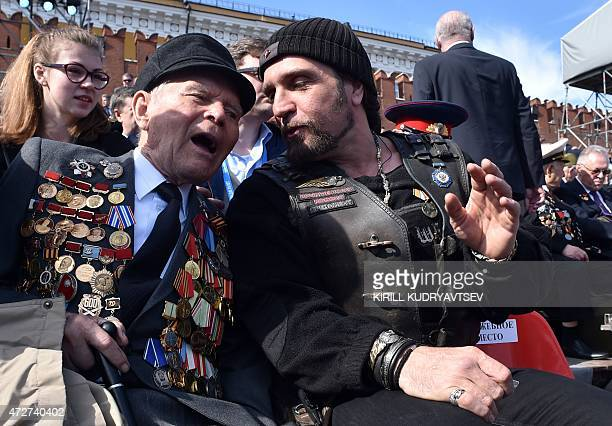 Alexander Zaldostanov also known as 'Khirurg' leader of the Night Wolves bikers' club speaks with a veteran before the Victory Day military parade at...