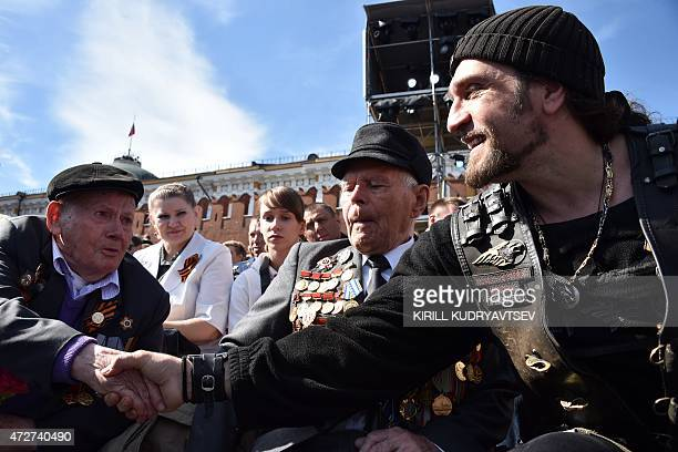 Alexander Zaldostanov also known as 'Khirurg' leader of the Night Wolves bikers' club shakes hands with a veteran before the Victory Day military...