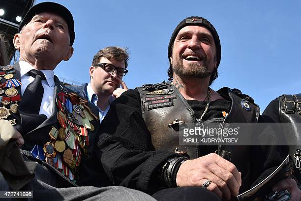 Alexander Zaldostanov also known as 'Khirurg' leader of the Night Wolves bikers' club smiles as he sits next to a WWII veteran before the Victory Day...
