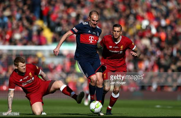 Alexander Zickler of Bayern Munich Legends skips over the tackle of John Arne Riise and Daniel Agger of Liverpool Legends during the friendly match...