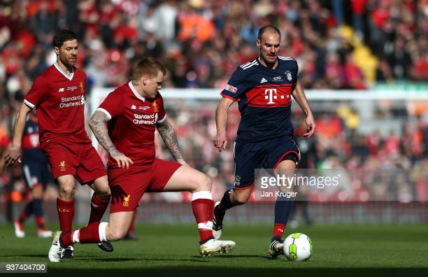 Alexander Zickler of Bayern Munich Legends skips over the tackle of John Arne Riise during the friendly match between Liverpool FC Legends and FC...