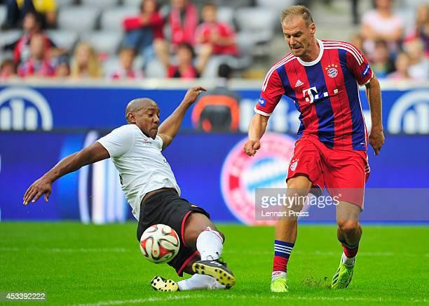 Alexander Zickler of FCB AllStars challenges Dion Dublin of ManUtd Legends during the friendly match between FC Bayern Muenchen AllStars and...