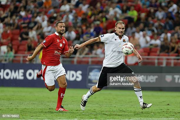 Alexander Zickler of Germany controls the ball as Luke Young of England gives chase during the Battle of Europe match between England Masters and...