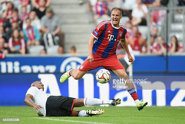 Alexander Zickler of Muenchen and Dion Dublin of Manchester compete for the ball during the friendly match between FC Bayern Muenchen Allstars and...