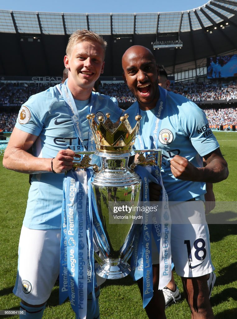 Alexander Zinchenko of Manchester City and Fabian Delph of Manchester City celebrates with The Premier League Trophy after the Premier League match between Manchester City and Huddersfield Town at Etihad Stadium on May 6, 2018 in Manchester, England.