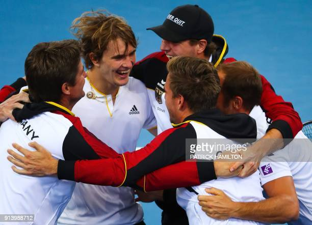 TOPSHOT Alexander Zverev of Germany and his team celebrate his victory over Nick Kyrgios of Australia following their forth round rubber of the Davis...