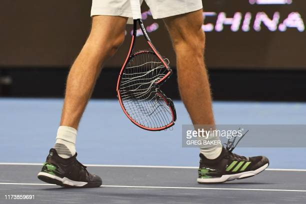 Alexander Zverev of Germany carries his racquet after smashing it during his men's singles semifinal match against Stefanos Tsitsipas of Greece at...