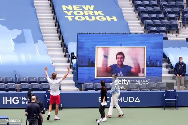 Alexander Zverev of Germany celebrates after with his brother Mischa Zverev on a Jumbotron after winning his Men's Singles first round match against...