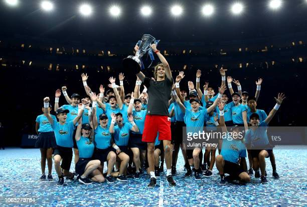 Alexander Zverev of Germany celebrates victory with the trophy and the ball boys and girls following the singles final against Novak Djokovic of...
