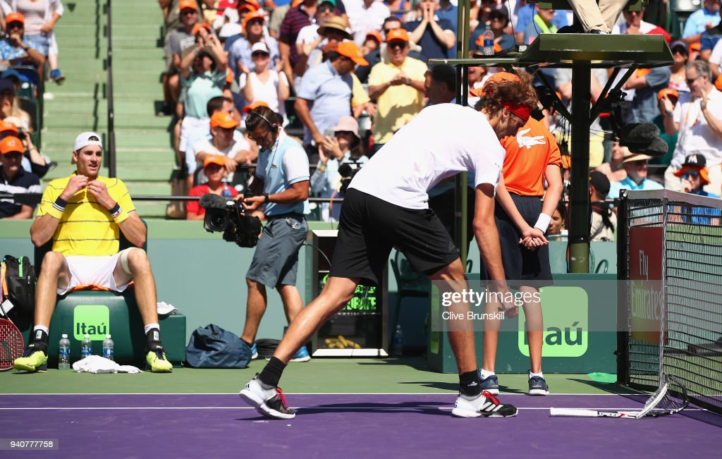 Alexander Zverev of Germany goes to pick up his smashed racquet against John Isner of the United States in the mens final during the Miami Open Presented by Itau at Crandon Park Tennis Center on April 1, 2018 in Key Biscayne, Florida.