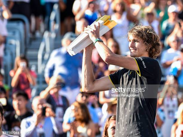 Alexander Zverev of Germany hoists the trophy up after defeating Roger Federer of Switzerland 63 64 during day ten of the Rogers Cup presented by...