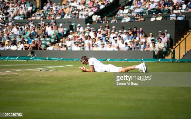 Alexander Zverev of Germany slips whilst in action against Ernests Gulbis of Lativa during The Wimbledon Lawn Tennis Championship at the All England...