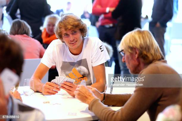 Alexander Zverev plays card with Carlo Thraenhardt during the 102 BMW Open by FWU at Iphitos tennis club on May 4 2017 in Munich Germany