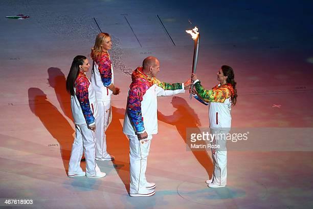 Alexandr Karelin hands the Olympic torch to Alina Kabaeva as Elena Isinbaeva and Maria Sharapova look on during the Opening Ceremony of the Sochi...