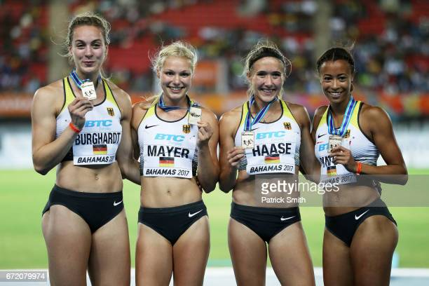 Alexandra Burghardt Lisa Mayer Rebekka Haase and Tatjana Pinto of Germany celebrate on the podium after placing first in the Women's 4x100 Metres...