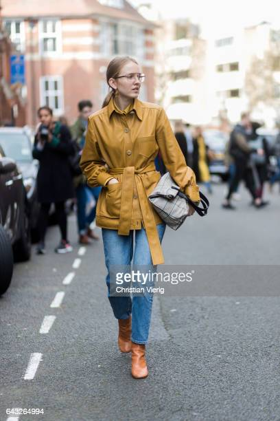 Alexandra Carl wearing a mustard belted coat denim jeans glasses outside Sharon Wauchob on day 4 of the London Fashion Week February 2017 collections...